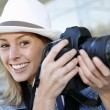 Beautiful woman photographer holding photo camera — Stock Photo