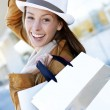 Cheerful girl in town holding shopping bags — Stock Photo