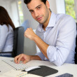 Stock Photo: Portrait of young office worker sitting at desk