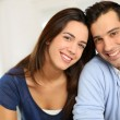 Portrait of cute young couple sitting in sofa — Stockfoto #26975449