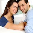 Portrait of cute young couple sitting in sofa — Foto de Stock
