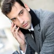 Trendy young businessman talking on mobile phone — Stock Photo
