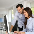 Stock Photo: Young office workers in front of desktop computer