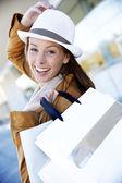 Veselá dívka ve městě drží nákupní tašky — Stock fotografie