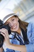Portrait of smiling girl holding photo camera — Stock Photo