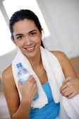 Young woman drinking water after exercising — Stock Photo