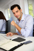 Portrait of young office worker sitting at desk — Stockfoto