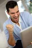 Man screaming in front of digital tablet — Stock Photo