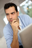 Puzzled young man using digital tablet — Stock Photo