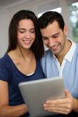 улыбаясь пара websurfing интернете с таблеткой — Стоковое фото