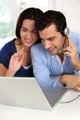 Cheerful young couple chating on internet with webcamera — Stock Photo