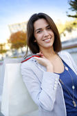 Smiling girl holding shopping bags in town — Stock Photo