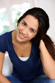 美丽的黑发女孩坐在沙发的肖像 — 图库照片