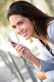 Young woman in town talking with handsfree — Stock Photo