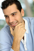 Portrait of young man with hand on chin — Stock Photo