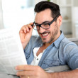 Cheerful guy reading newspaper in sofa — Stock Photo