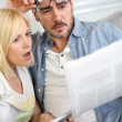 Couple reading news with horrified look — Stock Photo