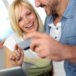 Cheerful couple at home doing online shopping — Stock Photo