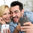 Cheerful couple having fun using smartphone — Stock Photo