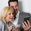 Couple using smartphone together — Stock Photo #27877663