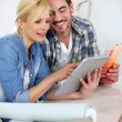 Middle-aged couple choosing wall colours for new home — Stock Photo