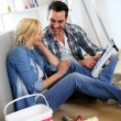 Stock Photo: Couple sitting on floor choosing paint colour