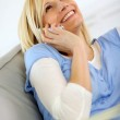 Beautiful blond woman laughing on the phone — Stock Photo
