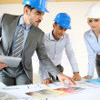 Stock Photo: Team of architects presenting construction project