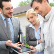 Real-estate-agent showing house plan on digital tablet — Stock Photo