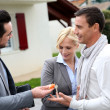 Salesman giving home keys to property owners — Stock Photo #27879523