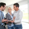 Middle-aged couple visiting house with salesman — Photo
