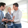 Stock Photo: Middle-aged couple visiting house with salesman