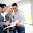 Middle-aged couple visiting house with salesman — Stock Photo #27879535