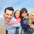 Portrait of cheerful family at the beach — Stok Fotoğraf #27879607