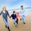 Family running on the beach — Stock Photo