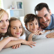 Family of four sitting in sofa at home — Stock Photo