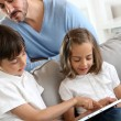 Children with daddy at home using digital tablet — Stock Photo