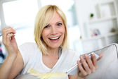 Smiling young woman at home using smartphone — Stock Photo