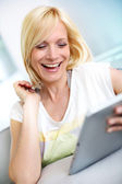 Smiling blond girl looking at tablet screen — Stock Photo