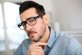 Trendy man with hand on chin looking at camera — Stock Photo
