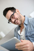 Middle-aged guy using digital tablet at home — Stock Photo