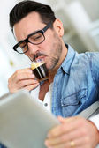 Man with glasses drinking coffee and using tablet — Stock Photo