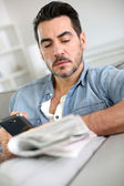 Man reading newspaper while using smartphone — Stock Photo