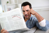 Man at home reading bad news on newspaper — Stock Photo