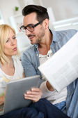 Couple reading news on both internet and paper — Stock Photo
