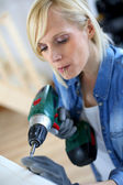 Woman at home using electric drill — Stock Photo