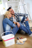 Couple sitting on the floor choosing paint colour — Stock Photo
