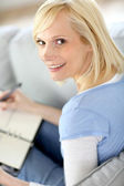 Young woman at home writing on agenda — Stock Photo