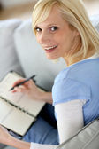 Blond woman in couch writing on agenda — Stock Photo