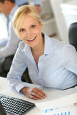 Cheerful businesswoman sitting in front of desktop — Stock Photo